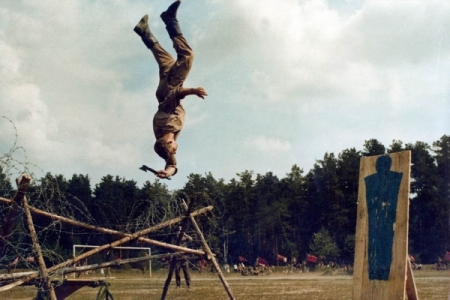A Spetsnaz soldier training to kill the enemy by backflipping over barbed wire and throwing a hatchet at a target with deadly accuracy.